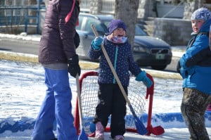 Kids and adults playing outdoor ice hockey