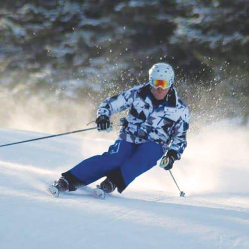Michael Botti skiing and kicking up powder