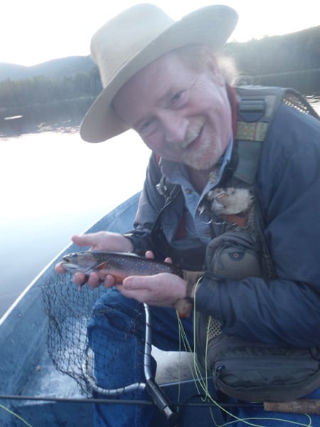 Peter Shea holding a small fish , whilst sitting in a boat on a lake
