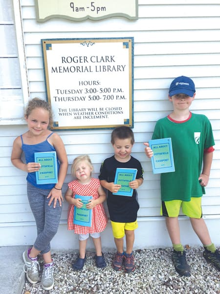 Pittfield youth posing under the Roger Clark Memorial Library Sign in Pittsfield
