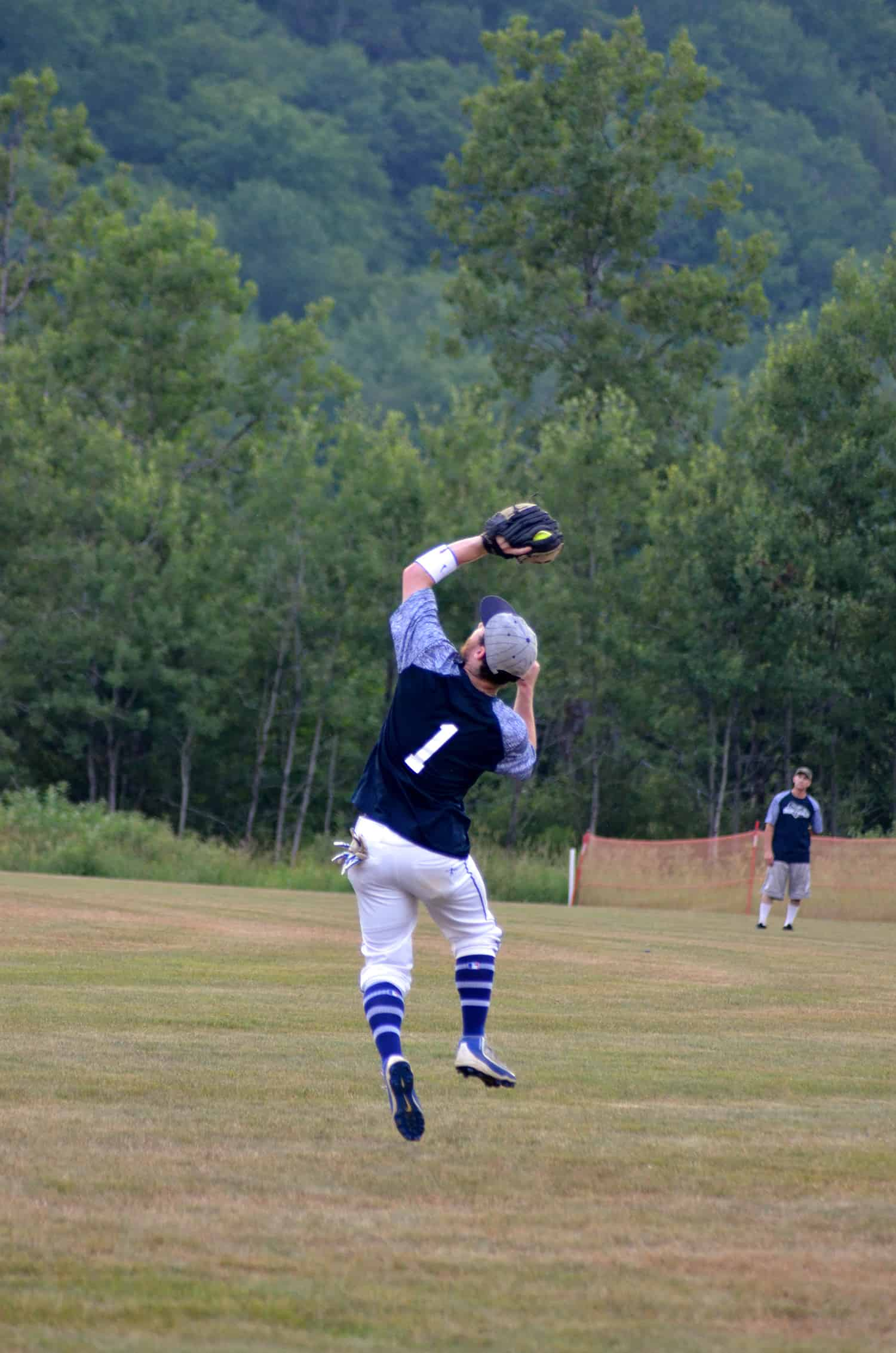 By Robin Alberti Donning No. 1, Clearly Moguls' right fielder Tucker Zink jumps for a catch, while Brandon Remmick looks on.